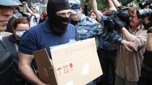 Des membres des services de police russe sortent avec des cartons de l'appartement du blogueur opposant Alexei Navalny, lundi 11 juin 2012 à Moscou.
