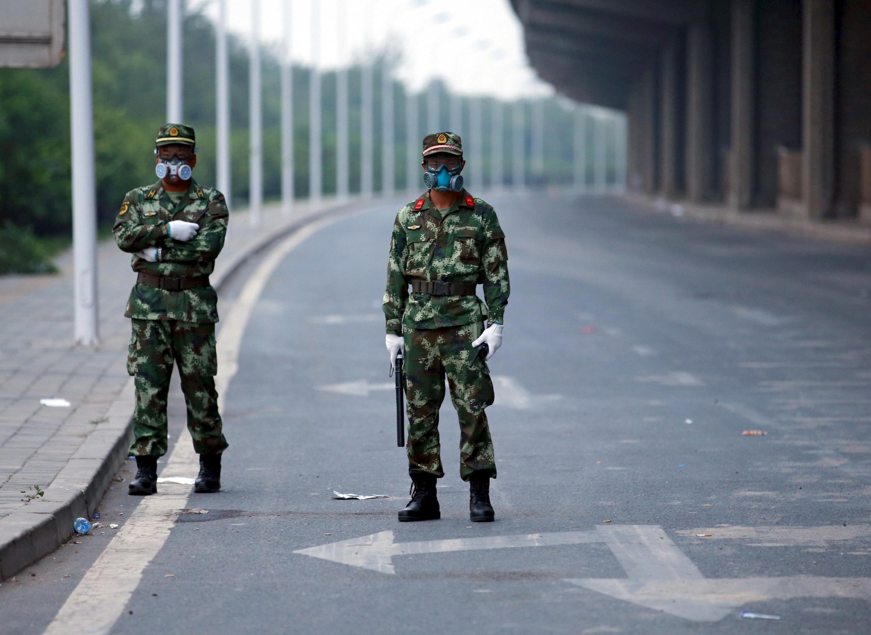 Des policiers gardent la route menant à la zone résidentielle évacuée et au site de la catastrophe dans le district de Binhai, à Tianjin.