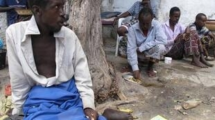 Chained patients under a tree as the rest of his comrades eat.