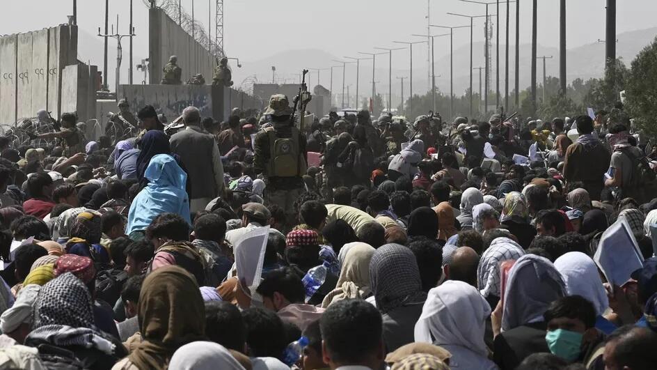 Des Afghans se rassemblent au bord d'une route près de l'aéroport de Kaboul