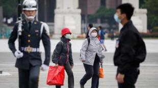 新冠肺炎疫情下,游客佩戴防护口罩走过台北中正纪念堂。摄于2020年3月11日
