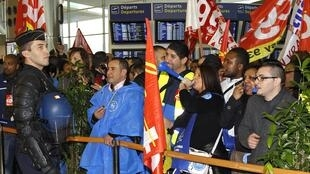 A French gendarme faces striking airport security staff at Roissy/Charles De Gaulle airport on Wednesday