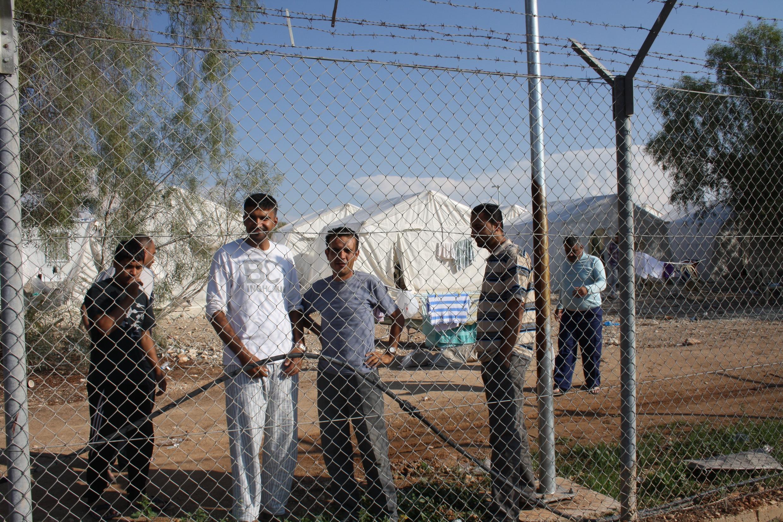 Des Syriens derrière les grilles du centre pour refugiés de Chypre.