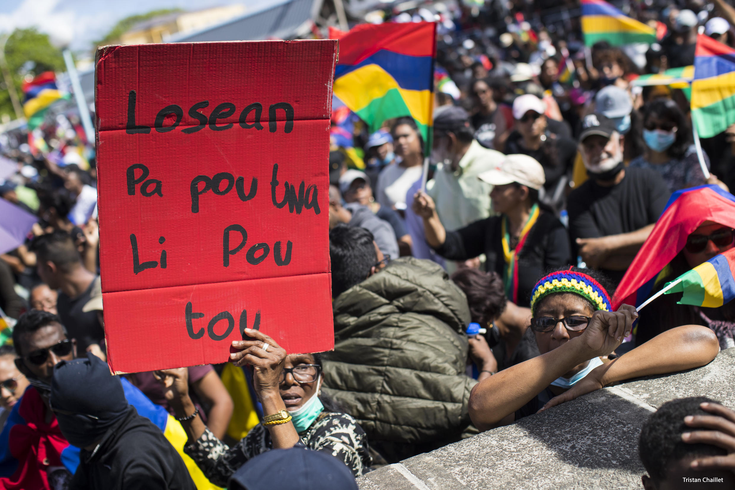 """Young and old walked together in the protest march in Mahebourg, a village south-east of Mauritius. Here an elderly lady holds a banner in creole that reads """"the ocean is not yours but for all""""."""