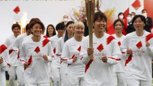 Las portadoras de la antorcha olímpica, del equipo nacional de fútbol femenino de Japón, encabezan el relevo en Naraha, Fukushima, el 25 de marzo de 2021