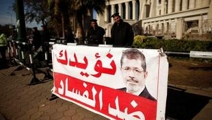 Wasu 'Yan sanda a kusa da hoton shugaba Muhammed Mursi na kasar Masar