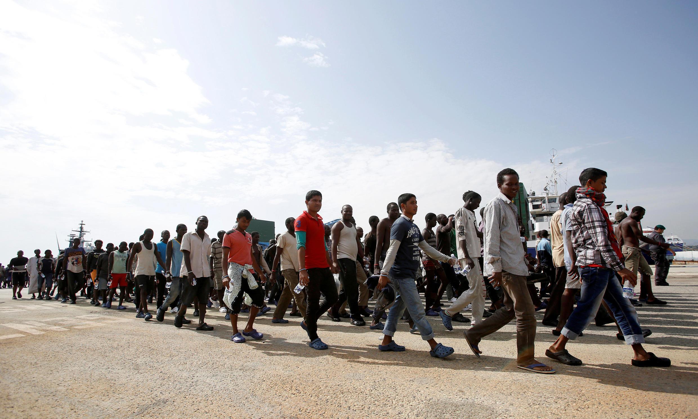 Un grupo de migrantes camina en el puerto siciliano de Augusta poco después de haber desembarcado del buque Bersagliare, este 16 de septiembre de 2016.