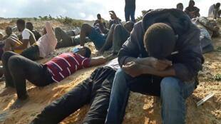 Migrantes sobreviventes do naufrágio em que morreram 74 pessoas permanecem em uma praia em Al Jums, uma cidade da Líbia a 120 km a oeste de Trípoli, em 12 de novembro de 2020.