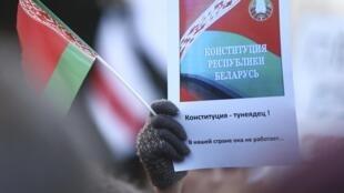 Un manifestant brandit une pancarte dénonçant la taxe controversée visant les citoyens qui travaillent moins de six mois par an, à Minsk, le 15 mars 2017.