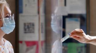 Un électeur montre sa carte d'identité à un assesseur dans un bureau de vote à Paris, dimanche 28 juin.