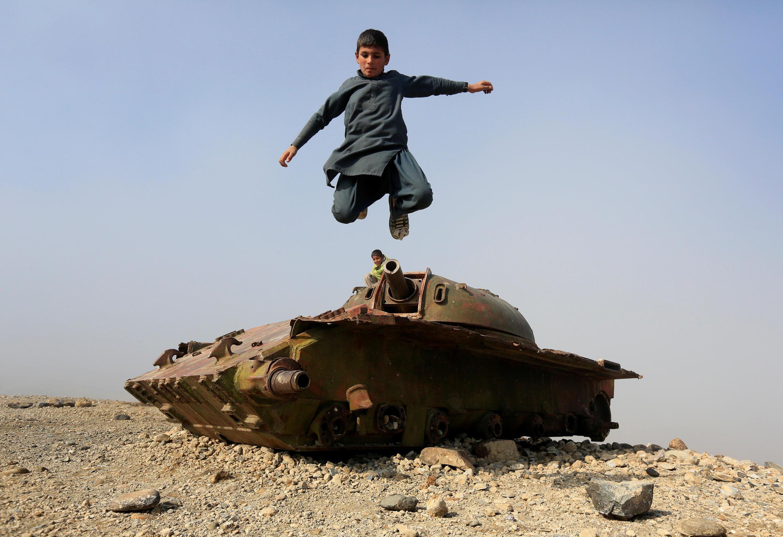 927 enfants ont été tués en Afghanistan en 2018: ils constituent le 1/3 du nombre total de victimes civiles selon les chiffres des Nations unies (photo: enfant sautant au dessus des restes d'un char soviétique, Jalalabad, le 15 février 2019).