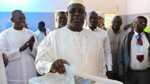 Le président sortant Macky Sall dépose son bulletin dans l'urne le 24 février 2019 pour l'élection présidentielle au Sénégal.