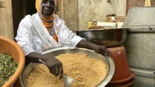 Aïssatou Cissé prépare la graine de couscous dans la cour de sa maison.