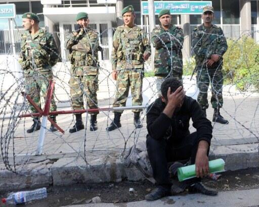 Un chômeur de Gafsa assis devant les bureaux de la CGP (Compagnie générale des phosphates) à Tunis gardée par des soldats le 30 novembre 2011.