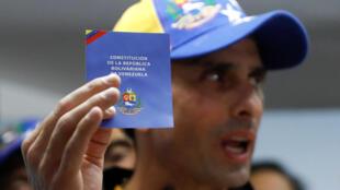 Henrique Capriles, figure de l'opposition, tenant une copie de la Constitution vénézuélienne, lors d'une conférence à Caracas le 6 avril 2017.