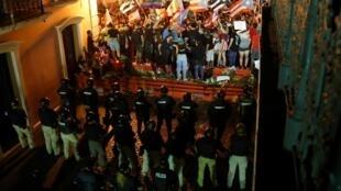 Los oficiales de policía hacen guardia frente a los manifestantes durante las protestas en las que se pidía la renuncia del gobernador Ricardo Rosselló en San Juan.