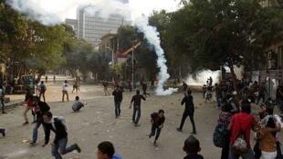 Manifestantes huyen de los gases lacrimógenos lanzados por la policía, cerca de la Plaza Tahrir, el 27 de noviembre en El Cairo.