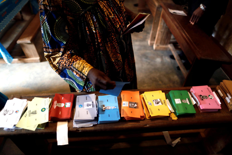 Une femme choisit le bulletin qu'elle va mettre dans l'urne dans un bureau de vote de Yaoundé le 7 octobre 2018.