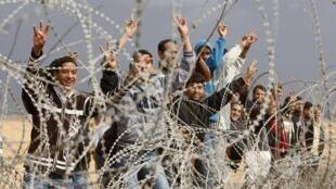 Grupo de palestinos vai até a cerca de segurança entre Israel e a Faixa de Gaza para cantar vitória aos soldados israelenses.