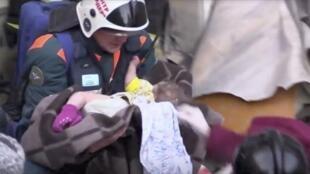 Bombeiro carrega bebê de 10 meses resgatada com vida após resistir a temperaturas glaciais de -27°C sob escombros de prédio impactado por explosão de gás nos Montes Urais.