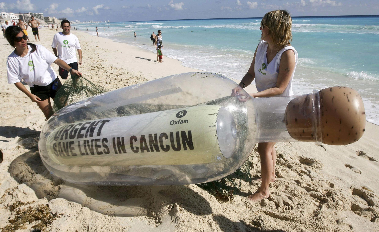 """Thành viên tổ chức phi chính phủ OXFAM triển lãm bày một cái chai khổng lồ trên bãi biển Cancun ngày 28/11/2010, bên trong có hàng chữ """"Khẩn cấp : Hãy cứu mạng người tại Cancun""""."""