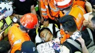 救護人員在被香港機場示威者打傷的大陸人身前