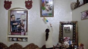 Sans titre «Death» 33, Palestine. Camp de réfugiés de Balata. Photos de K. Marchoud qu'est en train d'épousseter sa sœur dans le séjour de la maison familiale. Sur l'affiche, il est présenté comme le secrétaire général des Brigades des martyrs d'al-Aqsa.