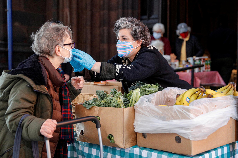 2021年3月20日,在美國紐約布魯克林的聖安和聖三一教堂的食品儲藏室中,一名志願者幫助分發新鮮食品時,幫助另一位婦女戴好口罩。
