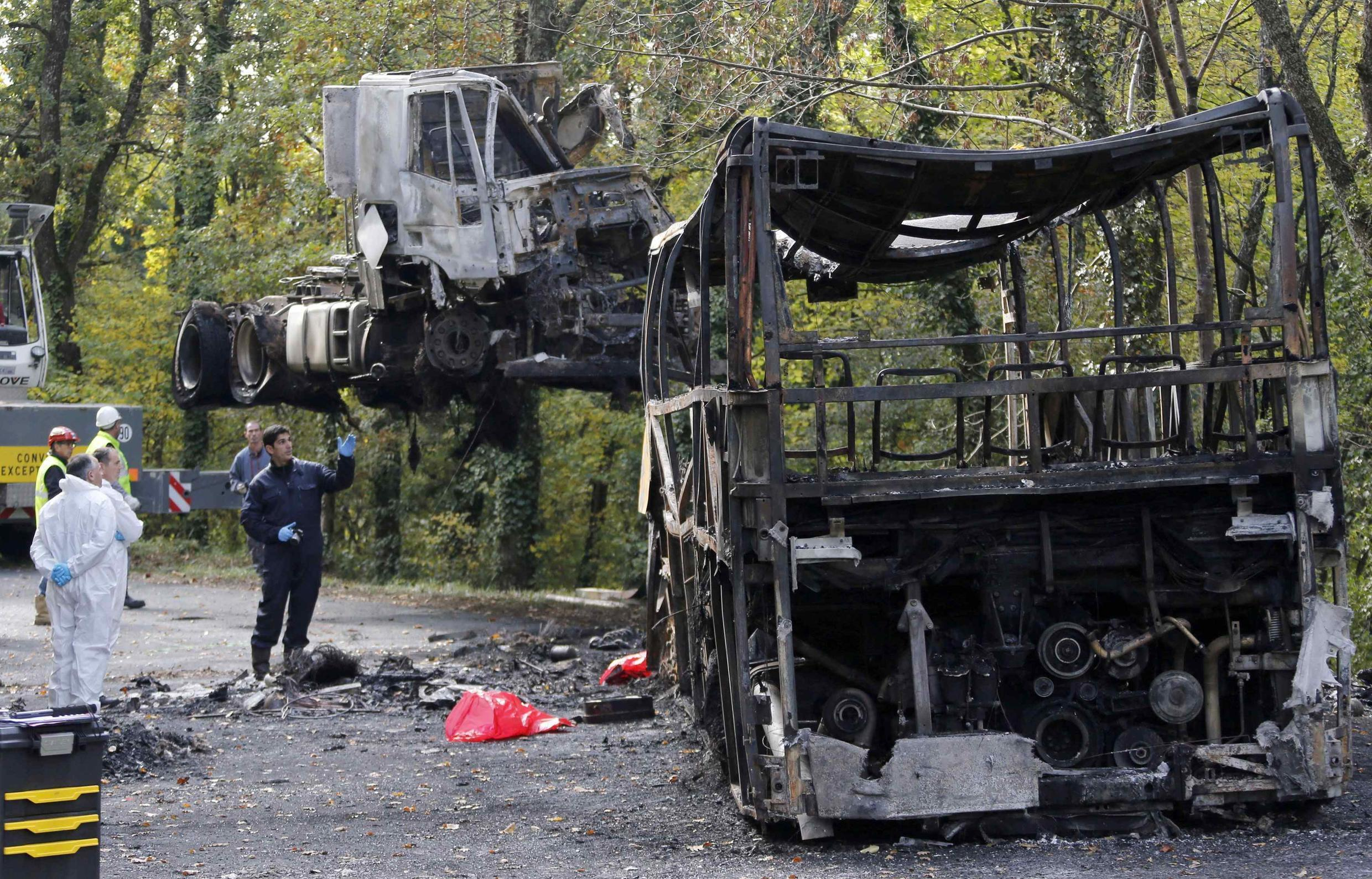 French gendarme investigators supervise the removal of the truck at the scene of the accident with a coach on a road near Puisseguin.