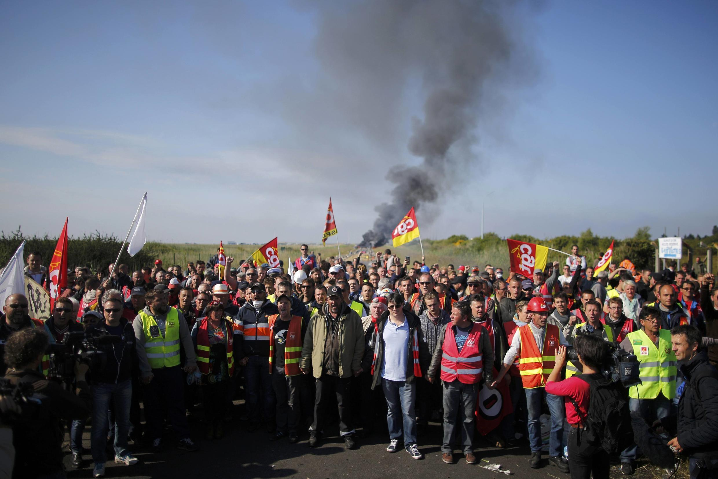 Striking French CGT labour union employees stand near a burning barricade before a police operation to free up a fuel depot near the Donges oil refinery last May