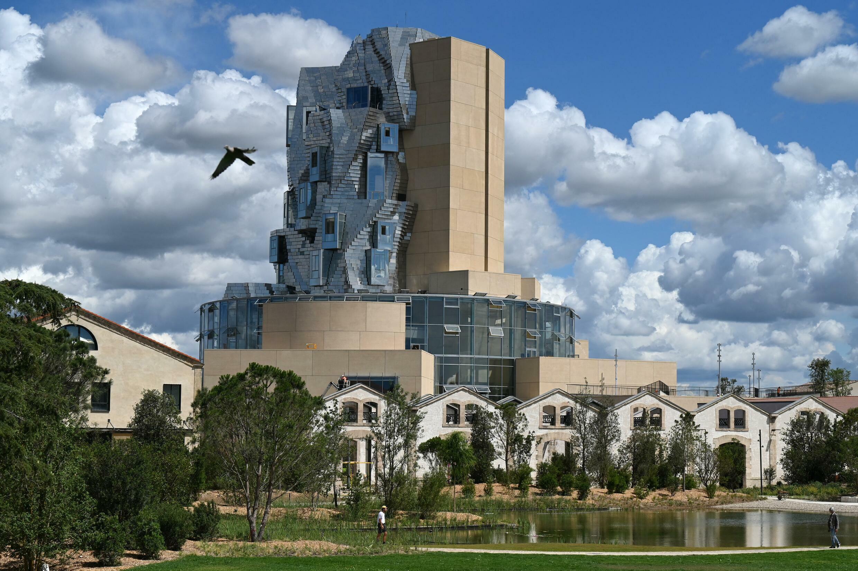 Photo prise le 24 juin 2021 à Arles, dans le sud de la France, montre une vue de la tour torsadée recouverte de tuiles d'aluminium réfléchissantes qui abrite la Fondation Luma, conçue par l'architecte canado-américain Frank Gehry. La Fondation Luma est située dans le Parc des Ateliers, un ancien atelier ferroviaire de la SNCF transformé en « campus ouvert pour la production créative, la présentation, l'étude et la préservation ».  © Pascal GUYOT / AFP