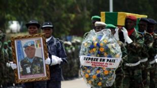 Des officiers de police et des membres de l'armée togolaise brandissent le portrait du sergent Landja Mozoboyo, l'un des cinq soldats togolais tués au Mali, au cours une commémoration à Lomé, le 8 juillet 2016.