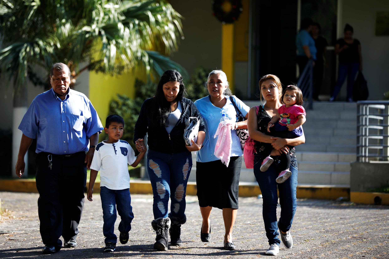 Una mujer deportada de Estados Unidos camina junto a su familia tras su llegada a San Salvador, 11 de enero de 2018.