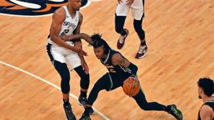 Ja Morant, des Memphis Grizzlies, dribble et écarte  Rudy Gay, des San Antonio Spurs, durant la rencontre entre les deux franchises le 19 mai 2021 à Memphis
