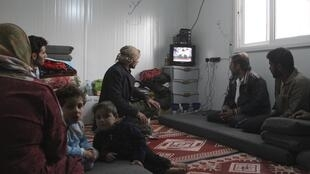 Syrian refugees watch a television broadcast of Syria's President Bashar al-Assad at the Al-Zaatari refugee camp in Jordania