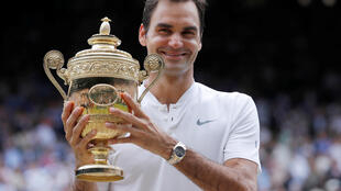 Switzerland's Roger Federer poses with the trophy as he celebrates winning the final against Croatia's Marin Cilic