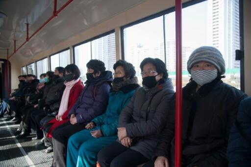 Commuters wearing face masks ride a tramcar in Pyongyang