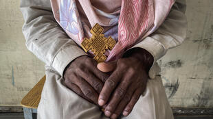 A priest, who did not wish to be identified, and said he was captured after trying to flee recent conflict and put in prison for two months and his best friend shot on the journey, sits with his Ethiopian Orthodox cross after arriving at a makeshift camp for displaced people in Shire, in the Tigray region of northern Ethiopia, 24 Feb 2021.