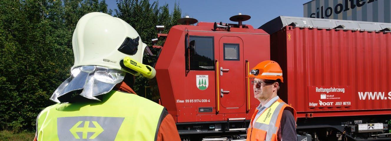 Des pompiers devant un train d'extinction et de sauvetage des Chemins de Fer Fédéraux suisses.