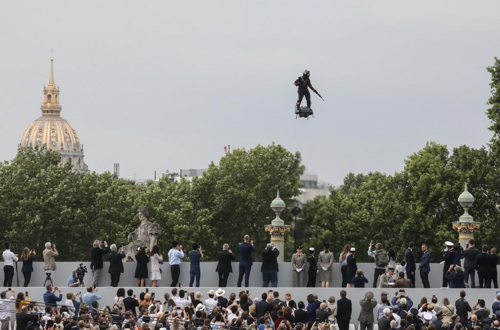 """French inventor Franky Zapata flies his jet-powered """"Flyboard"""" down the Champs-Elysees at the Bastille Day parade in Paris 14 July 2019."""