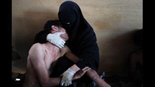 """""""荷賽獎""""評委團認為這張題為《懷抱的也門男子》的照片凝聚了阿拉伯之春運動的不同層面,而獲得本屆大獎。"""