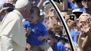 Le pape François embrasse un jeune enfant alors qu'il quitte le stade de Sarajevo après y avoir célébré une messe, le 6 juin 2015.