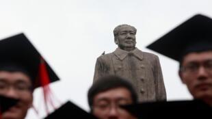 Graduados posam para foto em frente à estátua do líder chinês Mao Tsé Tung após sua cerimônia de formatura na Universidade de Fudan, em Xangai, 28 de junho de 2013.