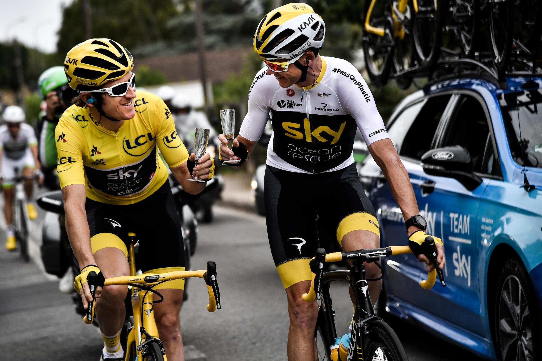 Британские гонщики Герейнт Томас (в желтой майке лидера) и Крис Фрум с бокалами шампанского