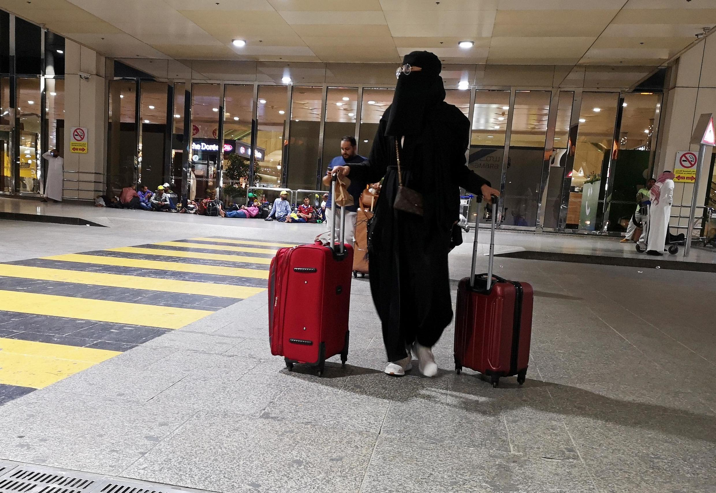 A Saudi woman walks with her luggage as she arrives at King Fahd International Airport in Dammam, Saudi Arabia, August 5, 2019.