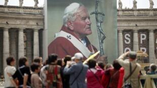 Fiéis em frente ao cartaz gigante de João Paulo II, colocado na praça São Pedro, em Roma.