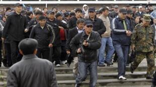 Lực lượng bảo vệ dọn đường cho tổng thống bị lật đổ Bakiev ra khỏi địa điểm mít tinh tại Osh, miền nam Kyrgyzstan.