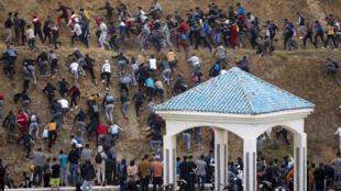 Decenas de migrantes huyen de la policía marroquí mientras tratan de alcanzar la ciudad española de Ceuta, el 18 de mayo de 2021 en la localidad marroquí de Fnideq