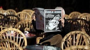 Un homme lisant le numéro du 6 janvier 2016 de Charlie Hebdo, à une terrasse de café à Nice.