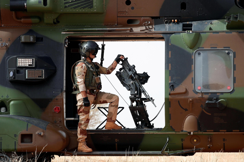 Un soldat français se tenant à côté d'une mitrailleuse montée alors qu'il surveillait la zone au cours de l'opération Barkhane régionale anti-insurgés dans Inaloglog, Mali, le 17 octobre 2017.